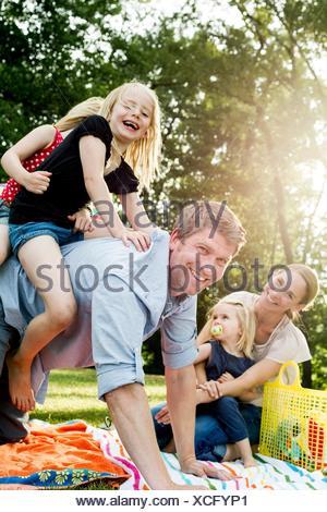Père filles donnant à dos pique-nique en famille dans la région de park Banque D'Images