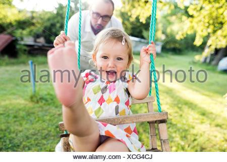 Père fille poussant sur swing in park Banque D'Images