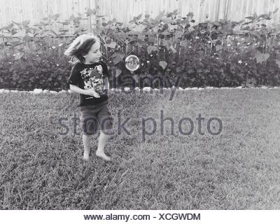 Cute Boy Standing On Grassy Field Banque D'Images