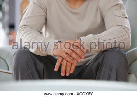 Mid section view of a man assise sur un fauteuil Banque D'Images