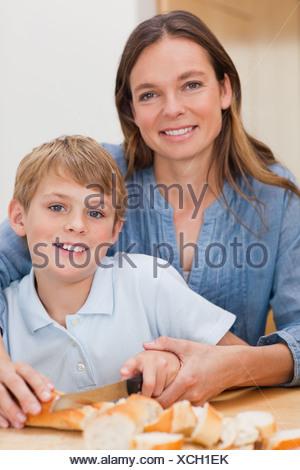 Portrait d'une mère de trancher le pain avec son fils Banque D'Images