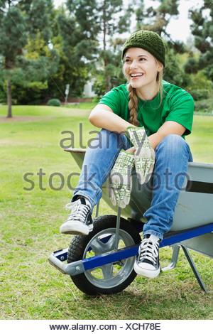 Toute la longueur de belle jeune écologiste assis dans une brouette à park Banque D'Images