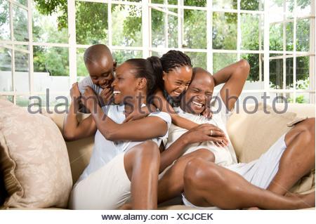 Jeune couple marié Africains jouent avec leurs deux enfants sur un canapé Banque D'Images