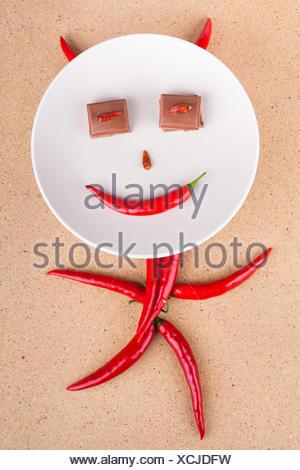 Heureux le piment fort caractère avec des yeux chocolat sur plaque, sur fond de bois. Banque D'Images