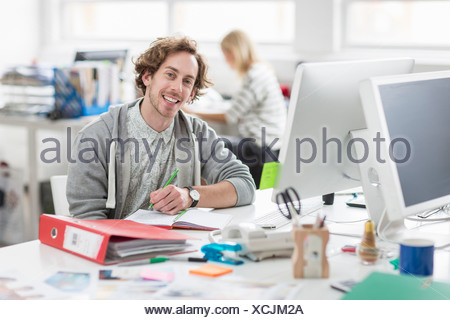 Young man sitting at desk and smiling in creative office, portrait Banque D'Images