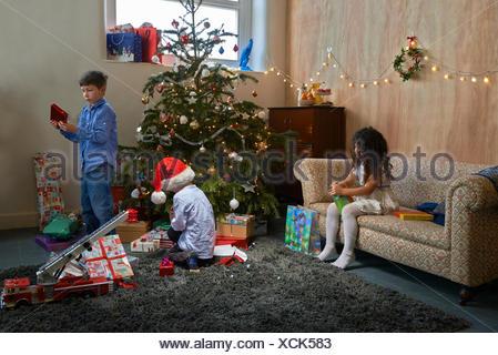 Fille et deux frères d'ouvrir les cadeaux de Noël dans la salle de séjour Banque D'Images