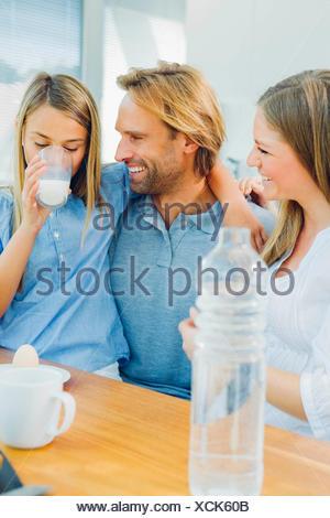 Heureux père et mère à la fille à boire du lait Banque D'Images