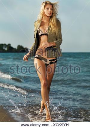 Young woman wearing bikini et d'un shirt de marcher le long de la plage Banque D'Images