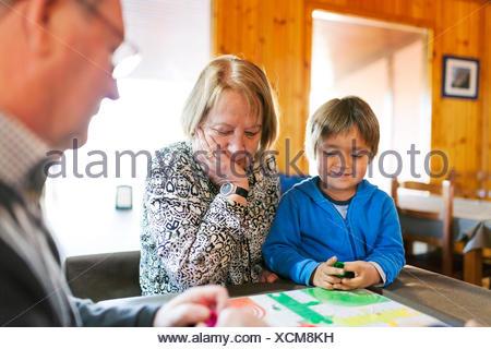 Les grands-parents jouer ludo leur petit-fils Banque D'Images