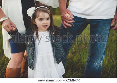 Jeune fille tenant son parent's hands, low section Banque D'Images