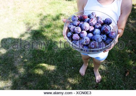 Close-up of a Boy holding a bowl de prunes Banque D'Images