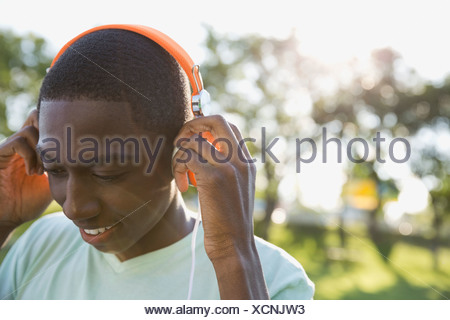 Teenage boy listening to music in park Banque D'Images