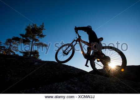 Silhouette d'Alex Leich avec VTT sur les Minimums de granit dans la région de North Conway, New Hampshire Banque D'Images