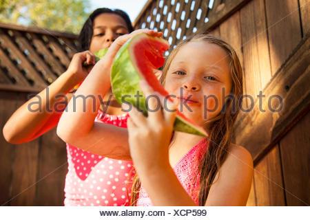 Deux filles de manger les tranches de melon dans jardin Banque D'Images