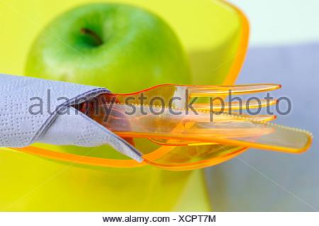 Bol en plastique, des couverts en plastique et de pomme verte Banque D'Images