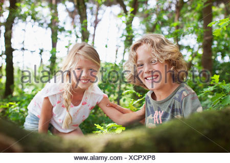 Boy and girl in forest looking at camera smiling Banque D'Images