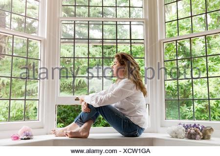 Portrait of young woman sitting on windowsill de salon à la fenêtre de Banque D'Images
