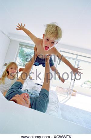 Père Fils de levage sur le lit dans la chambre Banque D'Images