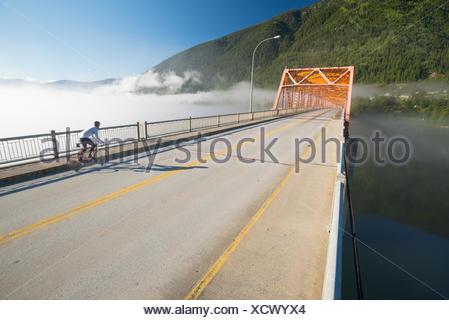 Un homme chevauche son vélo de route à faire la navette sur le grand pont orange à Nelson, BC Banque D'Images