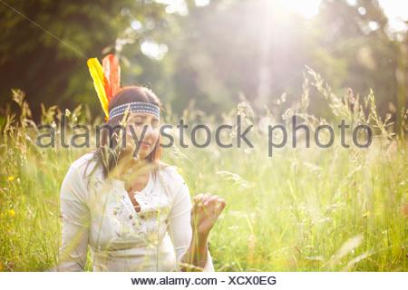 Mature Woman in native american coiffure dans l'herbe haute Banque D'Images