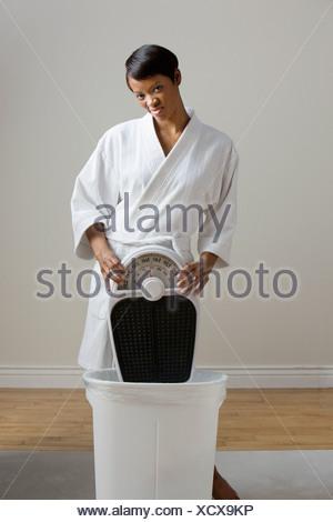 Jeune femme mettant un pèse-personne dans le bac Banque D'Images