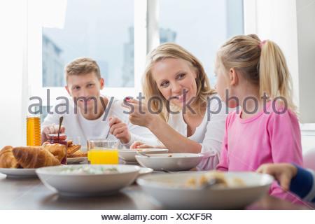 Une famille heureuse avec des enfants le petit-déjeuner à table Banque D'Images