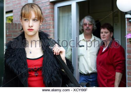 Adolescent de quitter la maison, en sortant. L'adolescente quitte, quitte les parents inquiets et confus à la porte avant. Banque D'Images