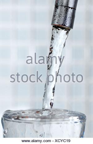 Close-up de robinet et verre d'eau contre l'arrière-plan flou Banque D'Images