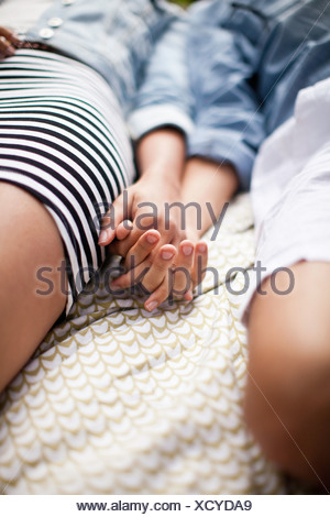 Young couple lying in park and holding hands, Close up Banque D'Images