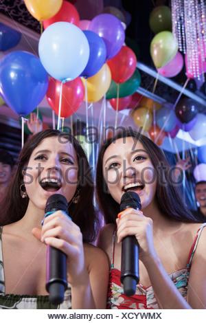 Deux amis holding microphones et chanter au karaoké, des ballons à l'arrière-plan Banque D'Images