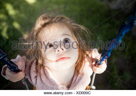 Baby Girl sitting on swing en plein air Banque D'Images