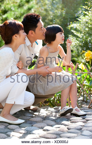 Family blowing Bubbles in garden Banque D'Images