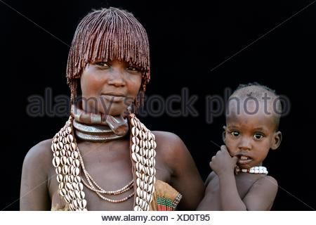 Jeune femme tribu Hamer avec colliers traditionnels et d'entendre l'objet avec un mélange d'ocre et de graisses animales, portant son bébé, Banque D'Images