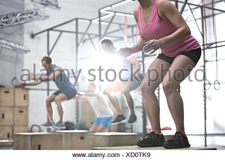 Les gens qui font de fort de l'exercice dans la salle de sport crossfit saut Banque D'Images