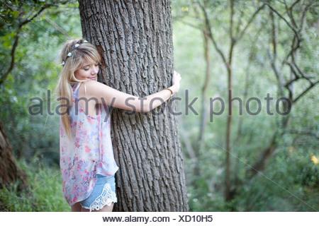 Teenage girl hugging tree à woodland Banque D'Images