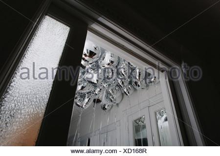Bouquet de ballons à l'hélium d'argent atteint le plafond d'une petite pièce Banque D'Images