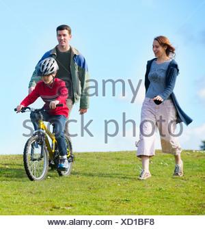 Les parents regardant son riding bicycle Banque D'Images