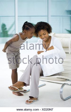 Femme assise dans une chaise, holding gift bag, fille debout à côté d'elle, à la fois à la bas Banque D'Images