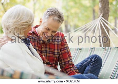 Mature Woman sitting in hammock at park au cours de l'automne Banque D'Images