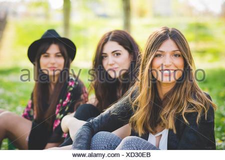 Portrait de trois jeunes femmes friends sitting in park Banque D'Images