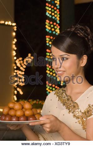 Woman holding bonbons dans une assiette et smiling