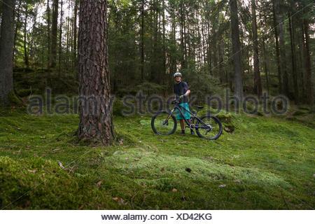 La Suède, Vastergotland, Lerum, Mature man with bicycle in forest Banque D'Images