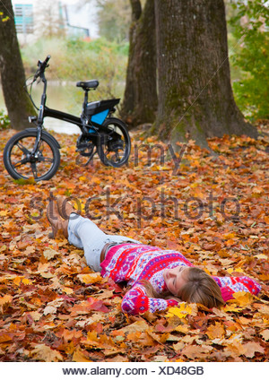 Woman laying in fall leaves Banque D'Images