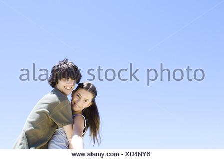 Serrant ses frère soeur, smiling at camera Banque D'Images