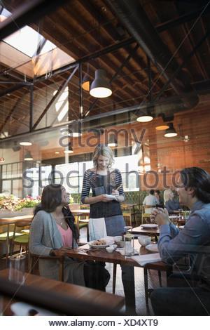 Serveur de l'ordre prise femelle couple at restaurant table Banque D'Images
