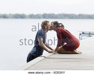Couple sur la jetée face à face tenant la main s'embrasser, Copenhague, Danemark Banque D'Images