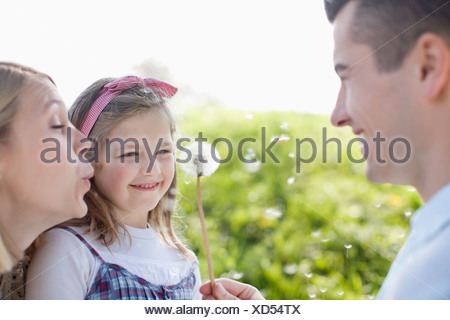 Family blowing dandelion spores Banque D'Images