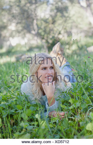 Woman lying on grass in garden Banque D'Images