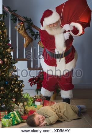 Père Noël en regardant le garçon endormi à côté d'arbres de Noël Banque D'Images