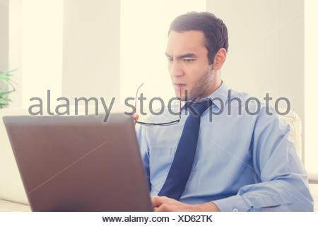 Fronçant man biting ses lunettes et à l'aide d'un laptop sitting on a sofa